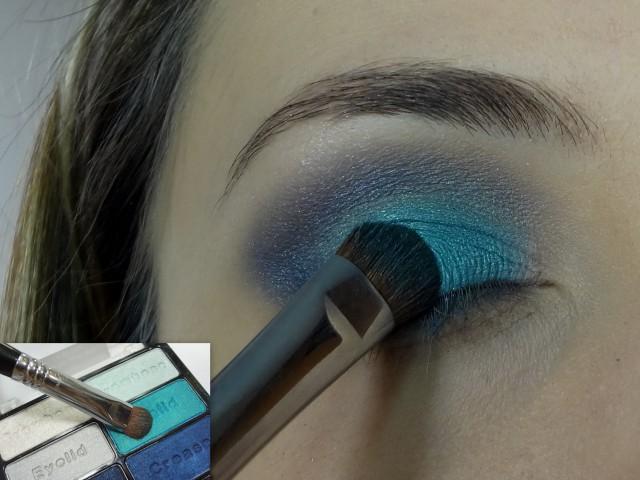 Com a sombra azul de destaque e um pincel de palpebra, aplico no centro do olho misturando a sombra escura do canto.