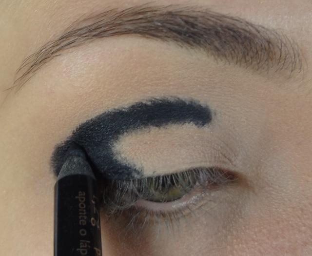 """Com a pele pronta, aplico um fixador de sombra. Depois com um lápis preto macio eu aplico no canto externo, marcando também na dobrinha do olho até """"quase"""" o canto interno."""